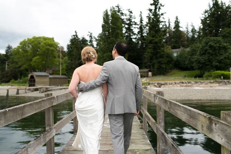 bride and groom walking down pier
