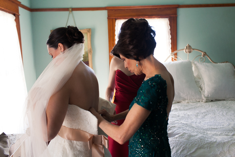bride and her mother putting on her dress