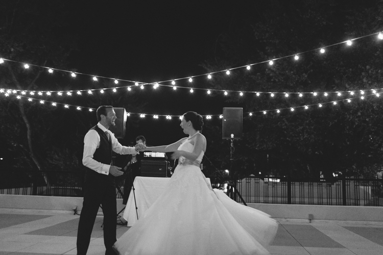 beautiful black and white wedding first dance string lights on the roof