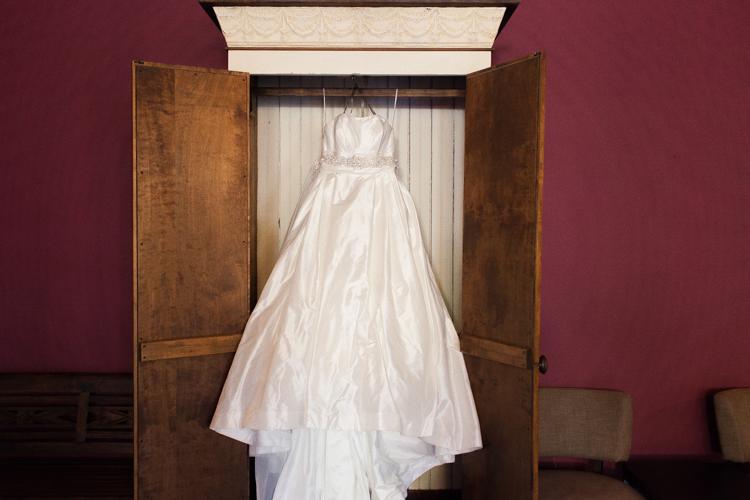 White wedding dress hangs in cupboard.