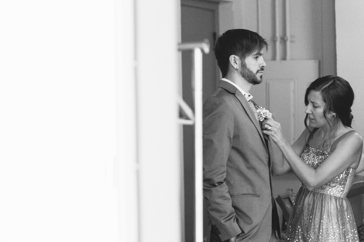 Black and white photo of bridesmaid helping groomsman with boutonniere.