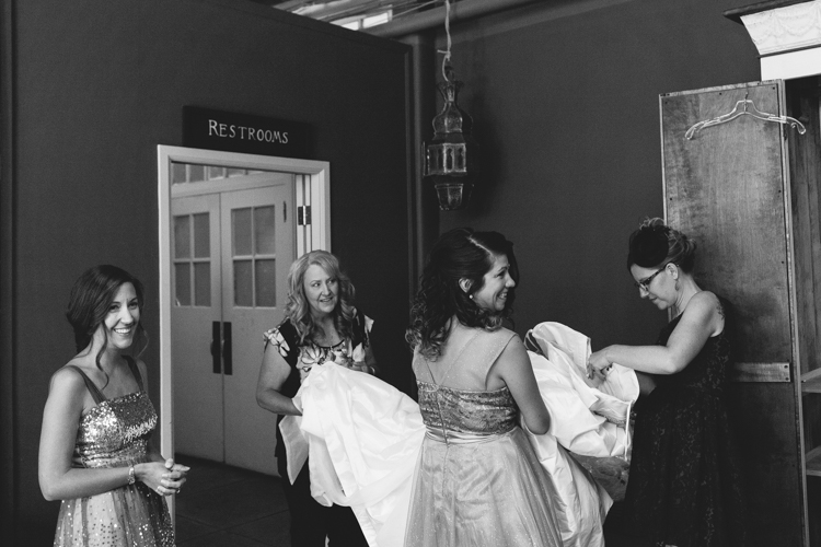 Smiling bridesmaids preparing to help the bride into her wedding dress.