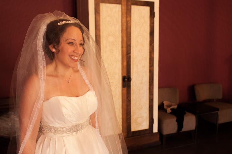A happy bride smiles after putting on her dress and veil at her wedding at The Hall at Fauntleroy in West Seattle, Washington.