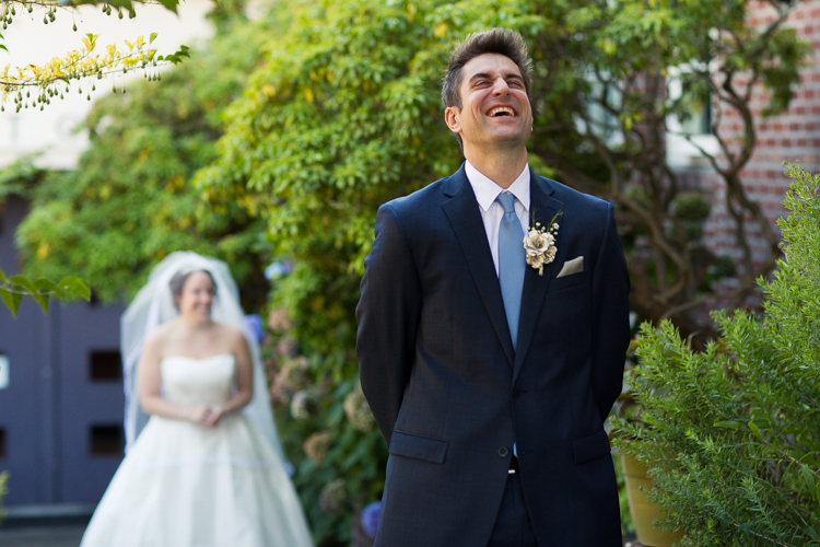 The groom laughs while waiting for his bride during their first look.