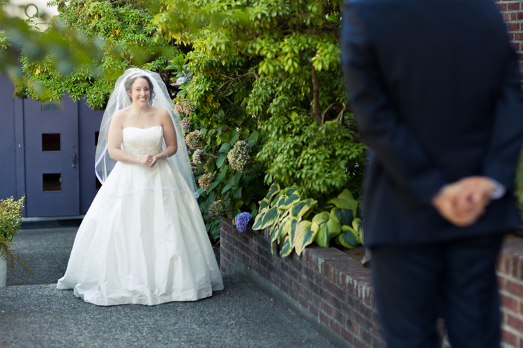 Groom turns to see the bride during their first look in front of The Hall at Fauntleroy.