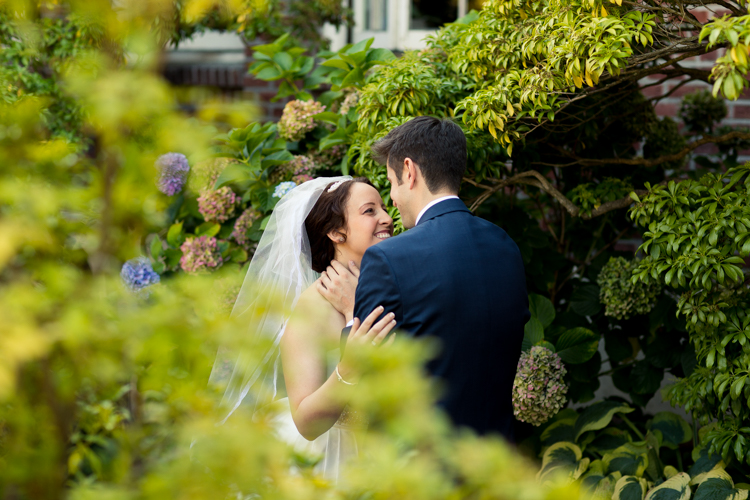 Bride and groom both smile as they embrace amongst the greenery in front of the Hall at Fauntleroy.