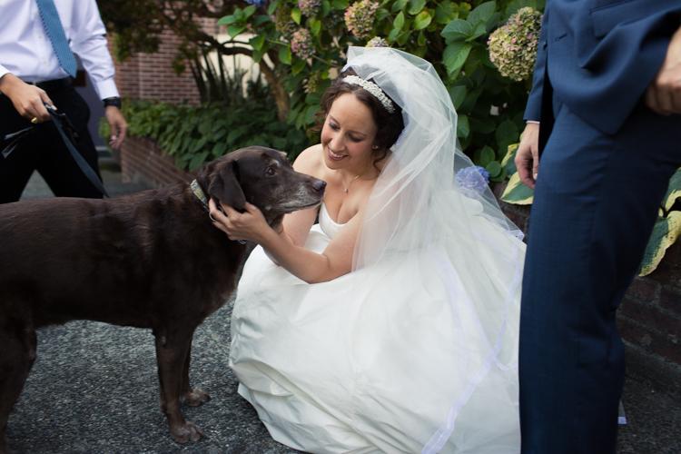 The bride kneels to pet her dog.