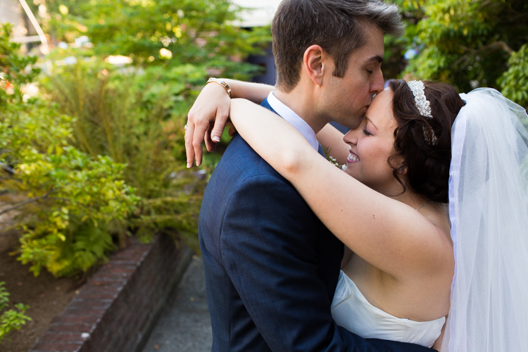 In a sweet moment, the groom softly kisses the bride's forehead.