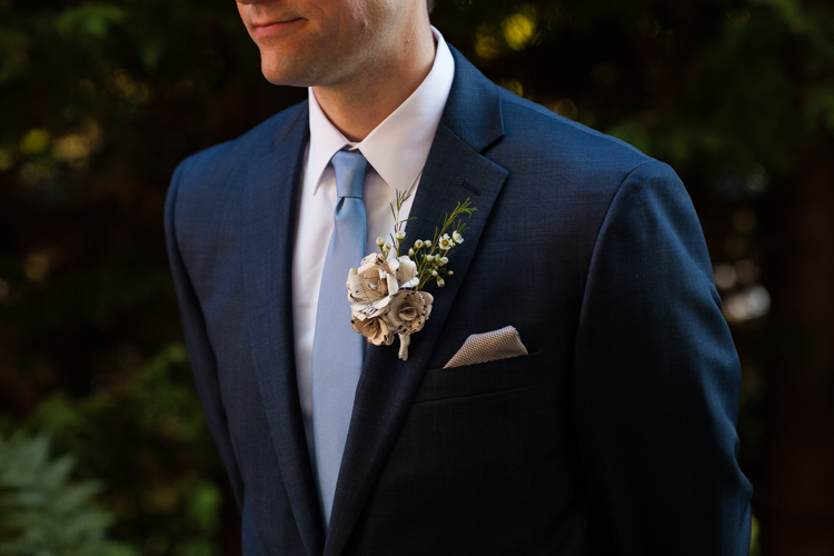 Close up detail photo of groom's paper flower boutonniere