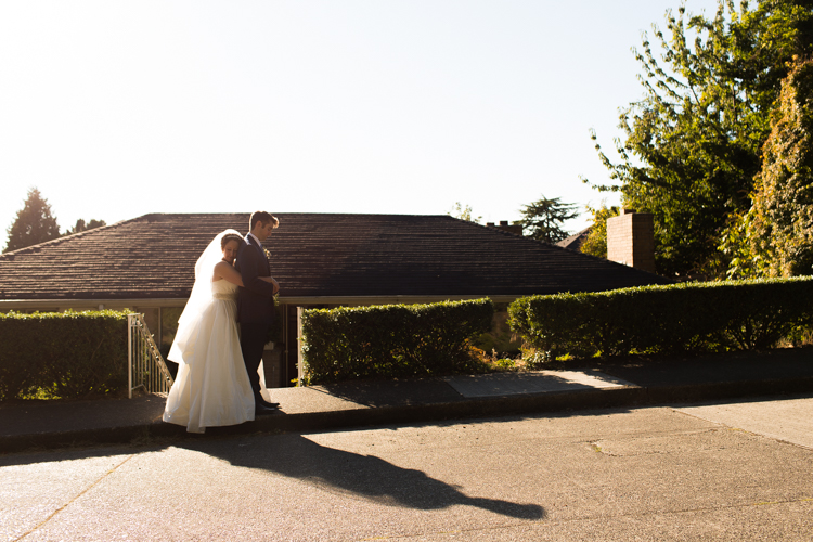 Bride hugs groom in front of setting sun.