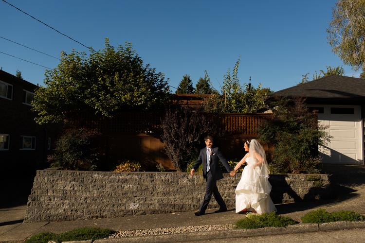 Groom and bride walking down West Seattle street before their wedding.