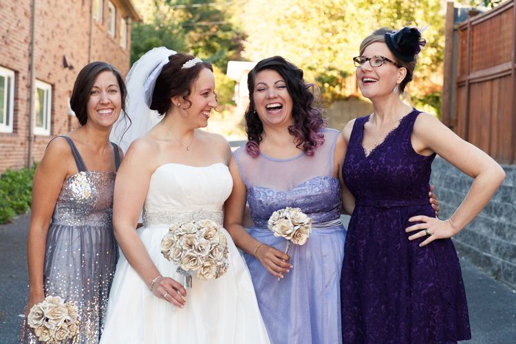 Laughing bride and bridesmaids in shades of purple holding paper flower bouquets made of sheet music.