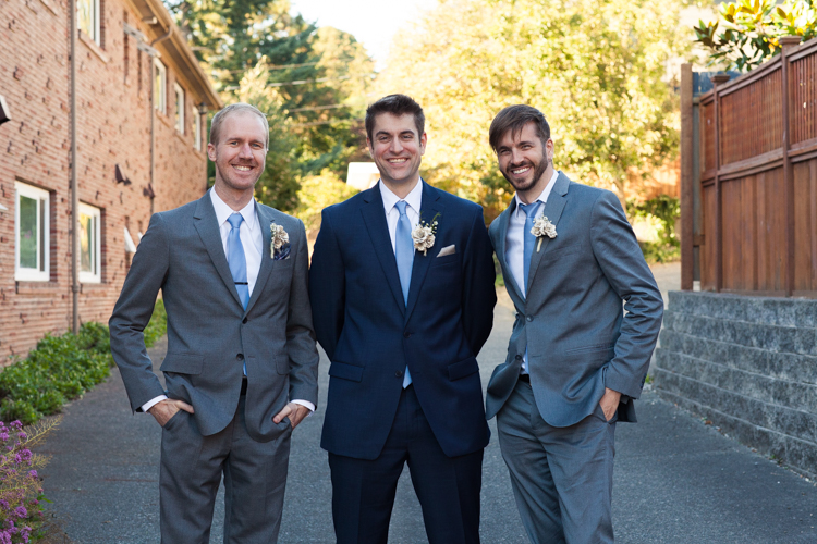 Groom and groomsmen smiling together wearing paper boutonnieres.