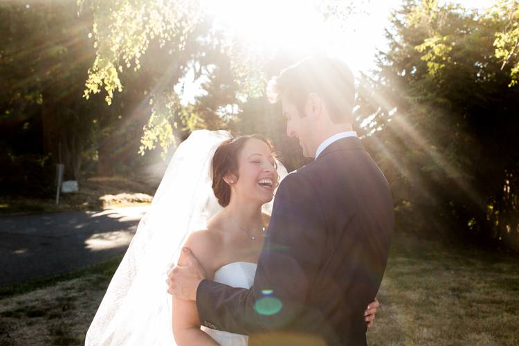 Bride laughing with groom during formals as the sun shines behind them.