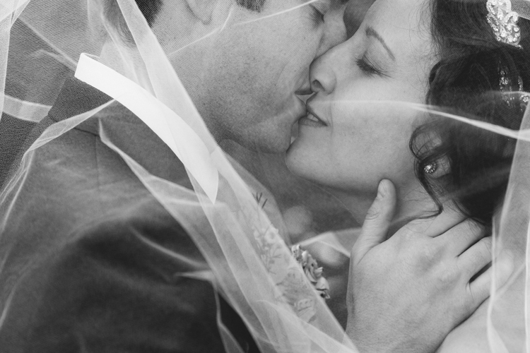 Bride and groom kissing under veil during formal photos.