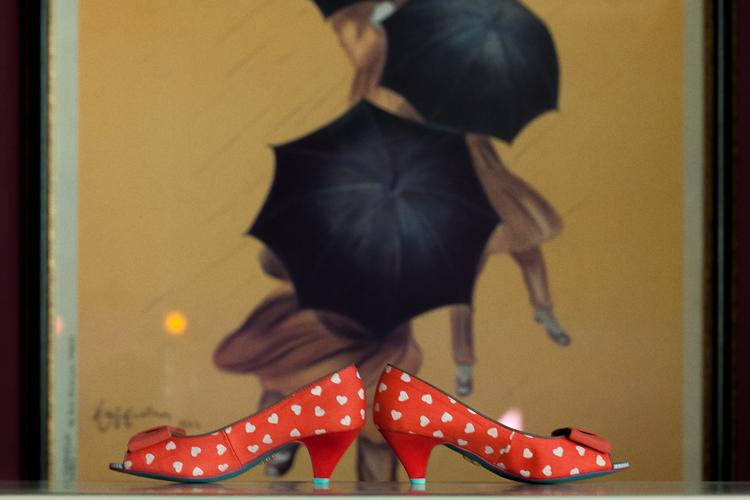 Polka dot bridal shoes in front of vintage poster.