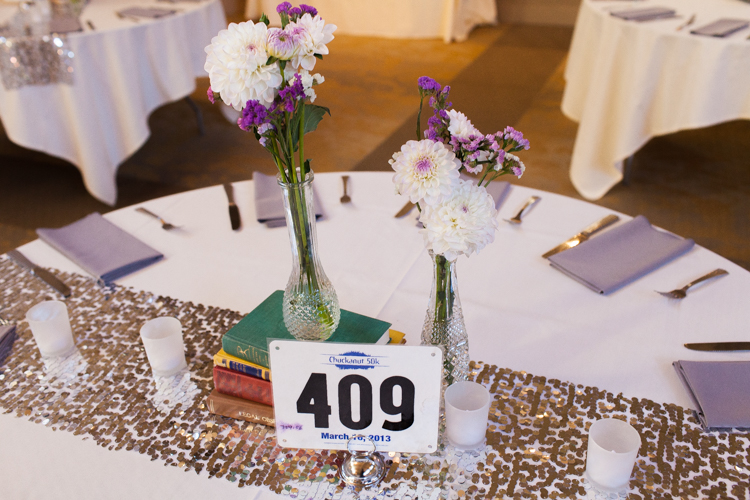 Wedding reception tables incorporating marathon bibs as table numbers.