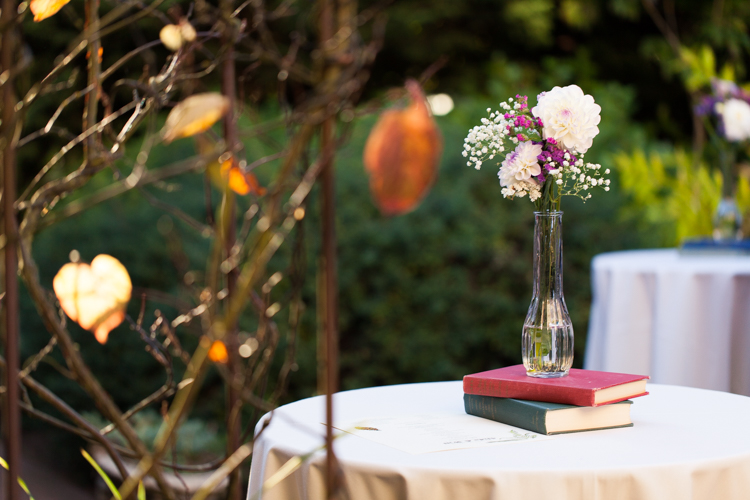 Using books and flowers in a vase as  wedding reception centerpieces.