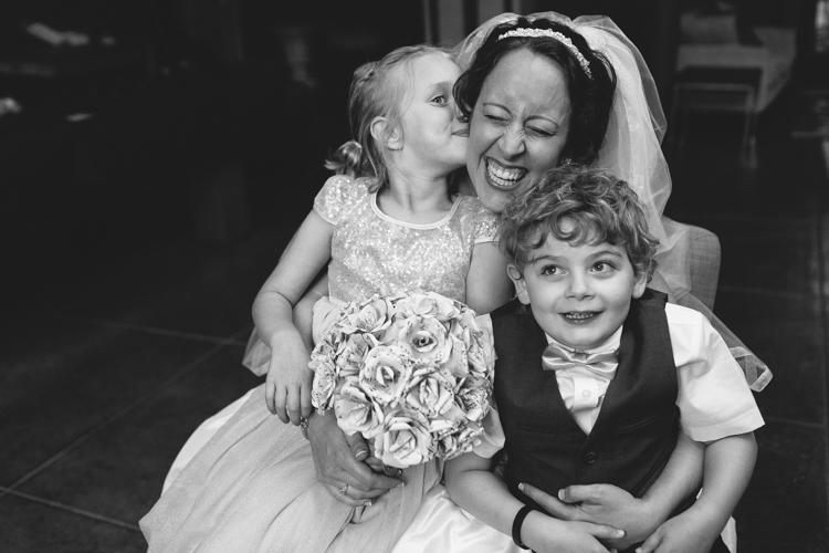 Bride hugging flower girl and ring bearer before wedding.