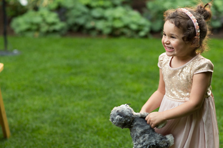 Smiling flower girl in gold dress with stuffed animal walking down the aisle.