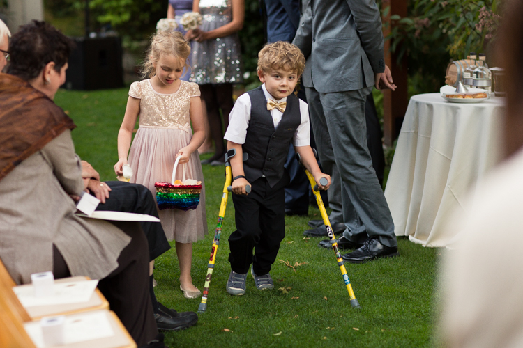 Flower girl with rainbow sequined basket and ring bearer wearing a gold bow-tie and vest.