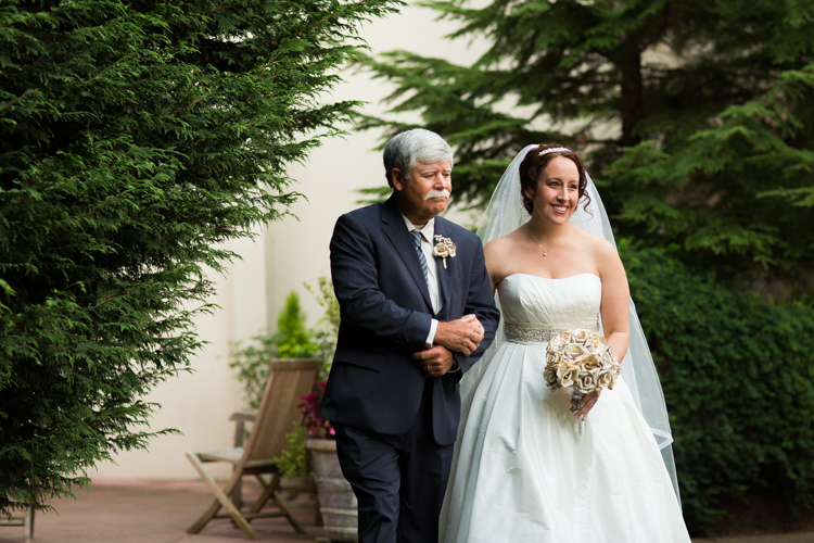 Bride and her father walking down the aisle in a sweet moment during the wedding ceremony.