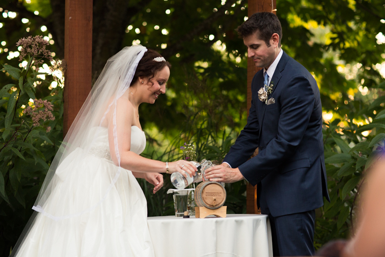 Bride and groom pouring whiskey into barrel for unity ceremony during wedding.