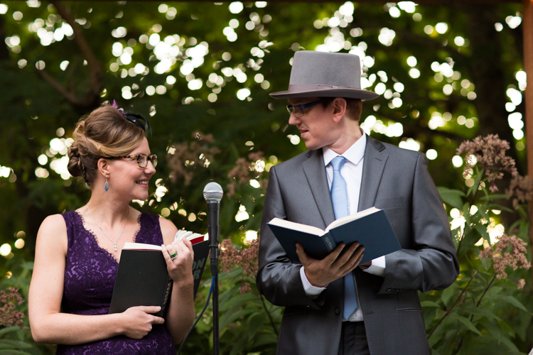 Two officiants at wedding ceremony. Male wearing grey top hat and female in purple lace dress.