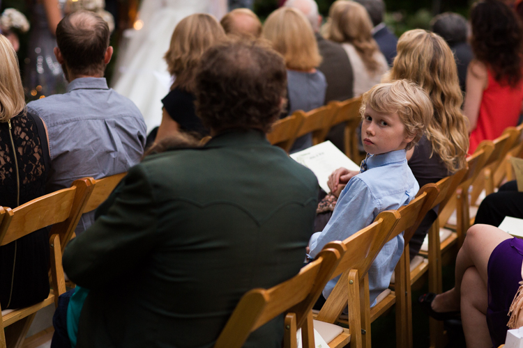 Child in blue shirt as guest during wedding ceremony.