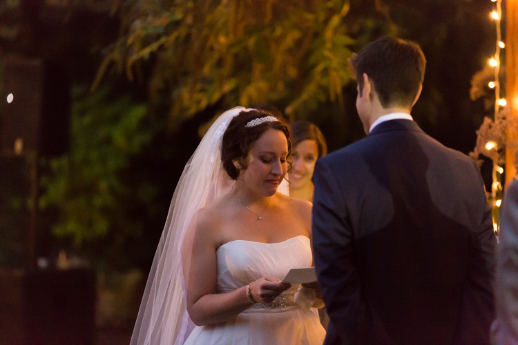 Bride cries during vows at string light lit wedding ceremony.