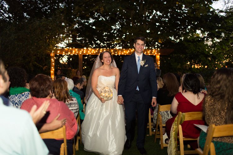 Newly married bride and groom walk up aisle together with beautiful lights behind them.