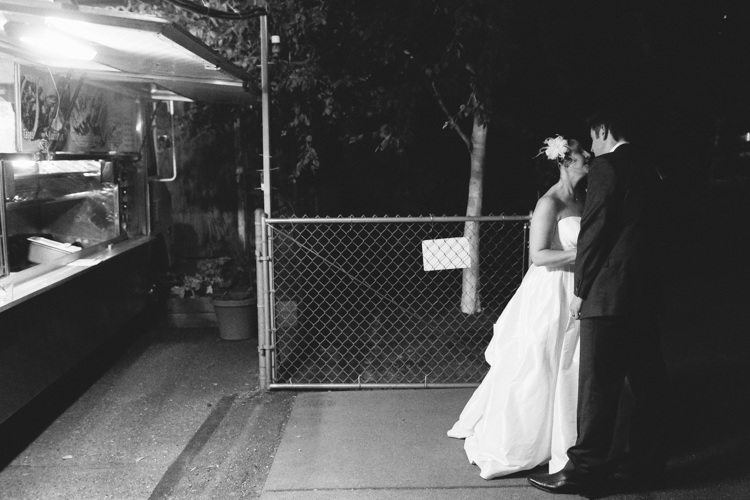 Bride and groom stand in front of taco truck during wedding reception.