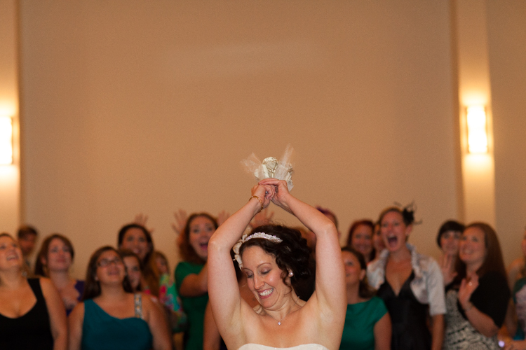 Bride throwing paper bouquet during wedding reception.