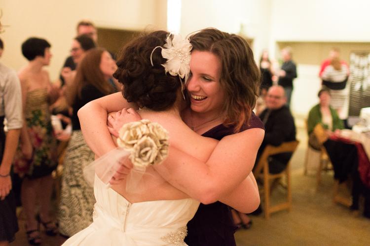 bride hugging guest during wedding reception