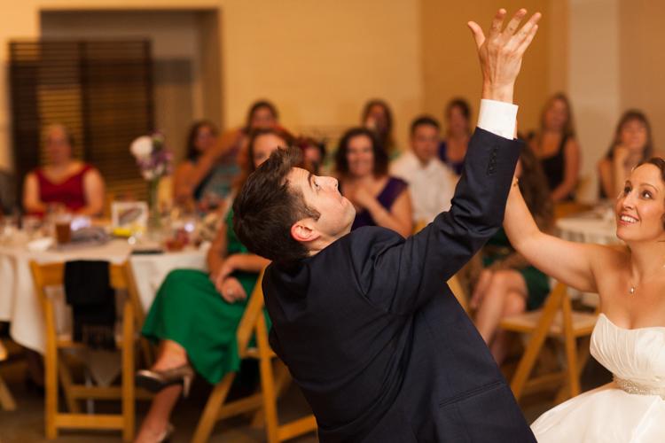 Groom tossing garter at wedding reception.