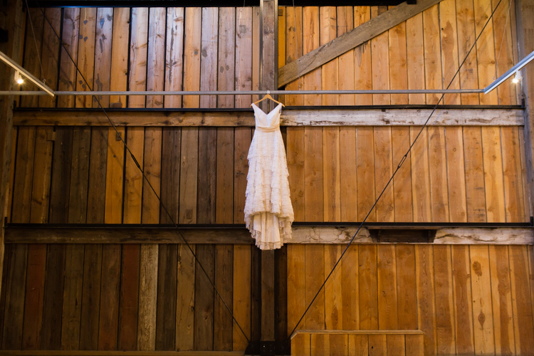 vintage bridal dress hanging from barn rafters