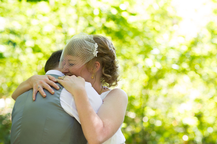 Bride and groom embrace in the woods.