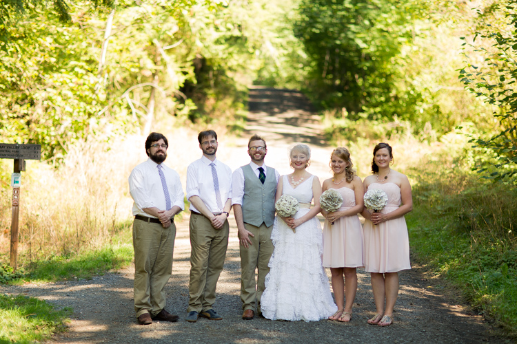 Wedding party with two bridesmaids and two groomsmen in light pink in the woods.