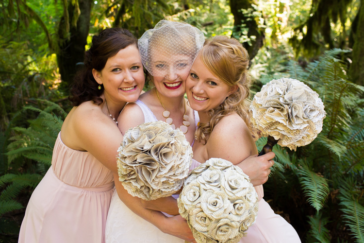 Bride and bridesmaids in light pink with paper flower bouquets.