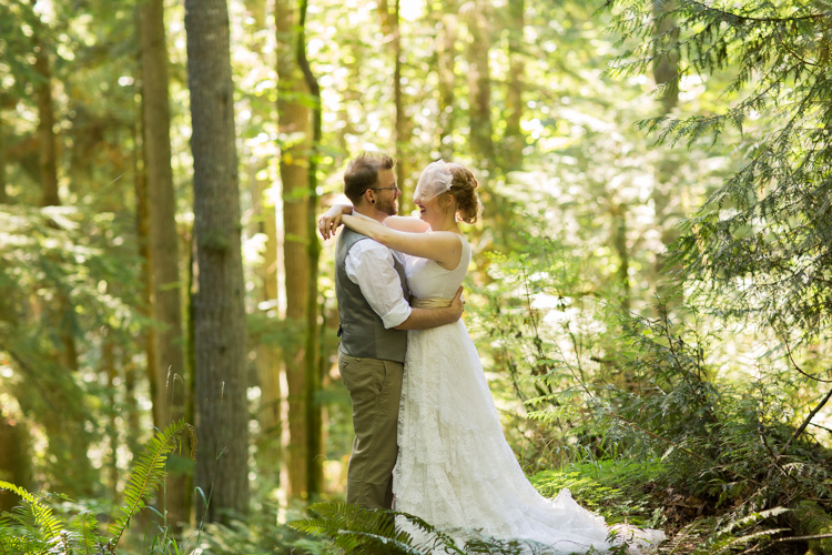 Bride puts arms around groom during formals deep in the woods.