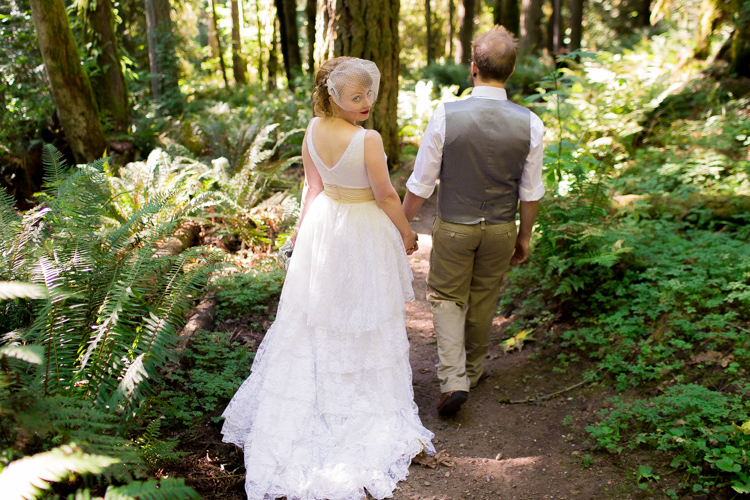 Bride looks back while walking hand in hand with groom through the forest.