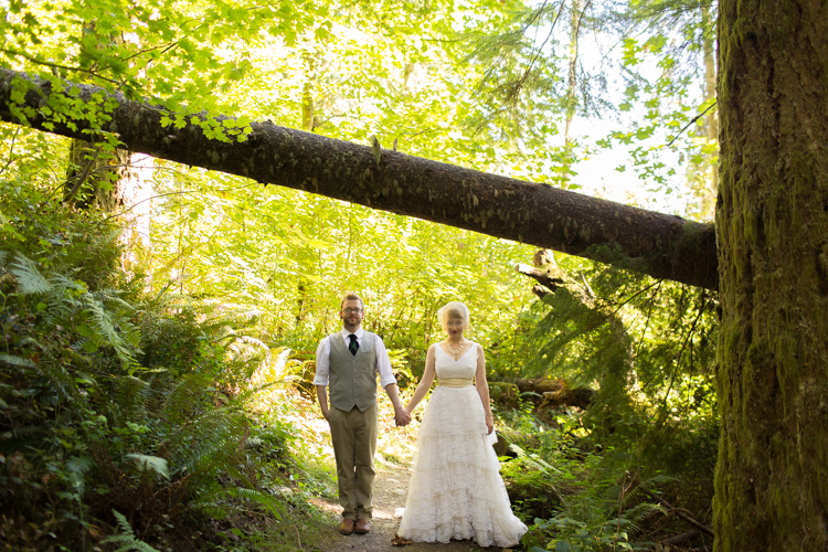 Bride and groom holding hands under fallen tree during formals in the woods.