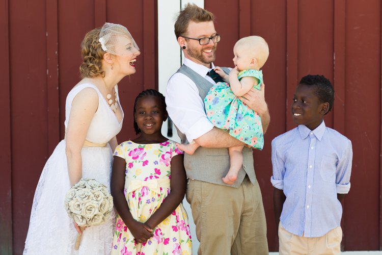 Bride and groom laughing with kids during family formals.