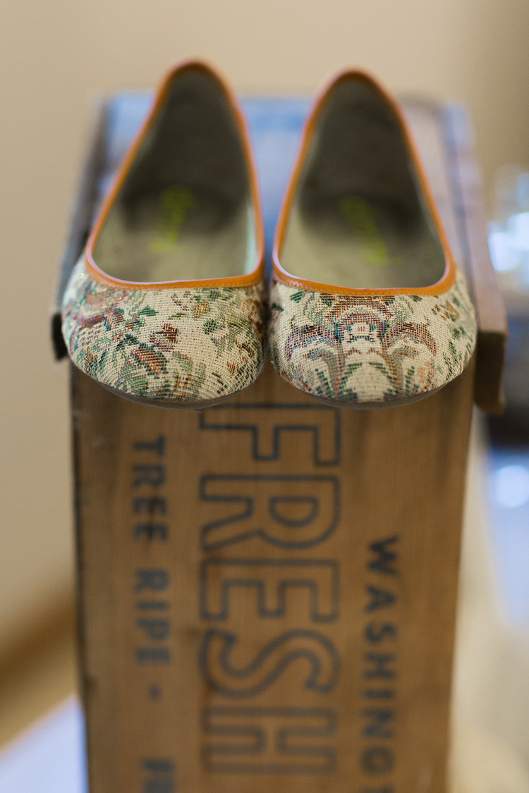 beaded wedding shoes sitting on apple box.