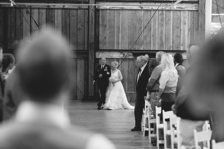 Bride and father walk down aisle during wedding ceremony at Pickering Barn in Issaquah, WA.