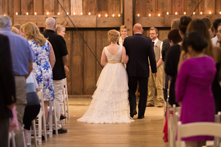Bride and her father walk down aisle during wedding ceremony at Pickering Barn.