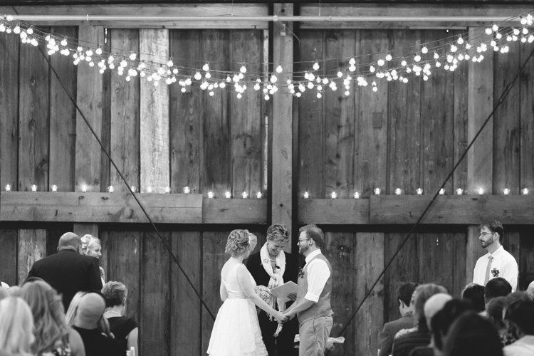 Bride and groom standing under twinkle lights during wedding ceremony at Pickering Barn.