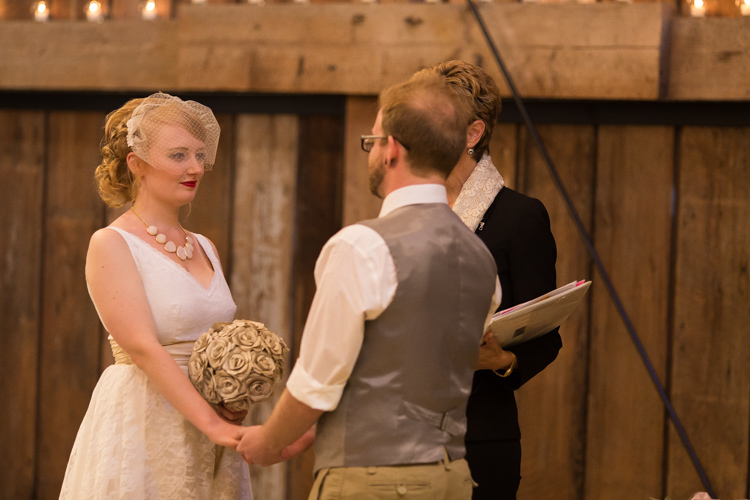Stylish bride and groom during wedding ceremony in old barn.