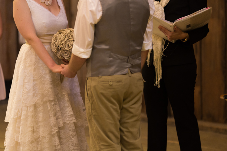 Bride and groom holding hands during ceremony in barn.