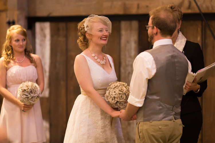 Bride smiling at groom during wedding ceremony in classic barn.